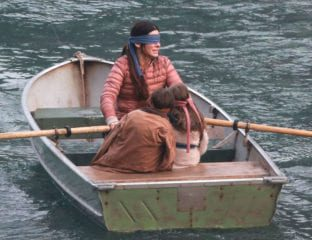 A woman and a pair of children are blindfolded and make their way through a dystopian setting along a river in 'Bird Box'.